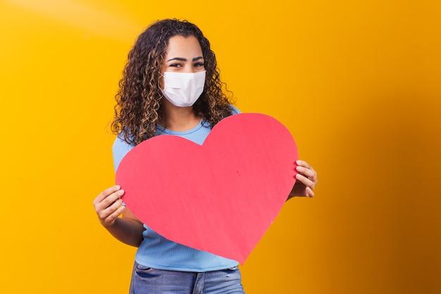 Młoda kobieta w masce chirurgicznej trzyma ogromne papierowe serce z miejscem na tekst.