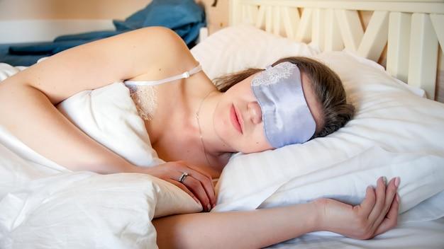 Młoda kobieta w masce do spania na oczach leżąca w łóżku rano