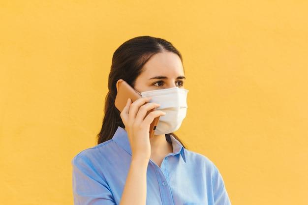 Młoda kobieta w masce i niebieskiej koszuli rozmawia przez telefon na żółtym tle