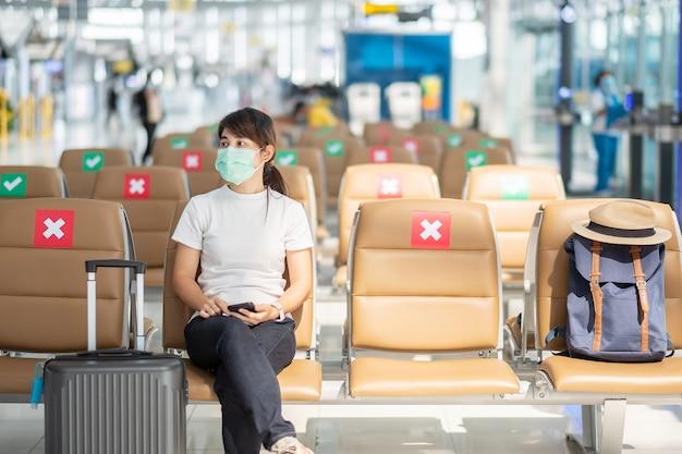 Młoda kobieta w masce i siedząca na krześle na lotnisku, ochrona przed zakażeniem koronawirusem (covid-19), podróżniczka z azji. nowa normalność, bańka podróżna i dystans społeczny