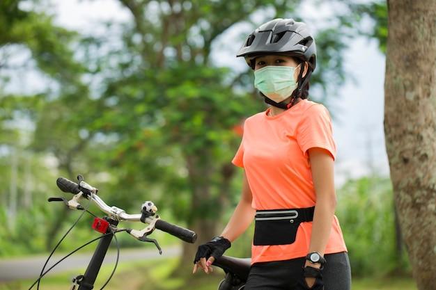 Młoda kobieta w masce medycznej jeździ na rowerze