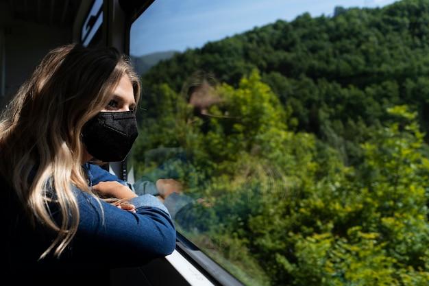 Młoda kobieta w masce medycznej patrząca na piękny widok natury