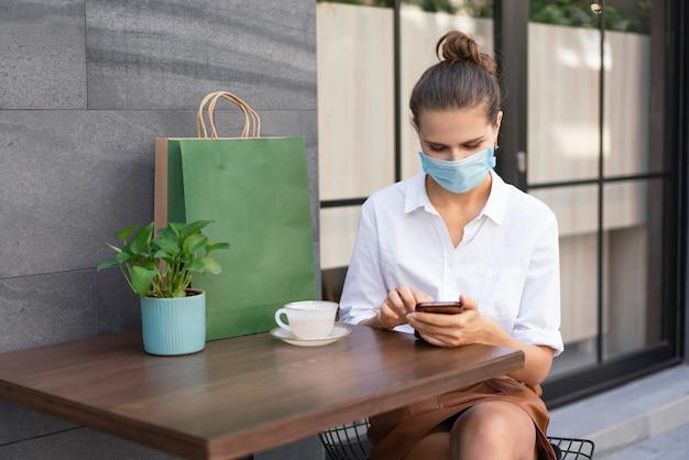 Młoda kobieta w masce medycznej w celu ochrony przed koronawirusem lub chorobą covid-19, siedząc i używając smartfona w ulicznej kawiarni na zewnątrz