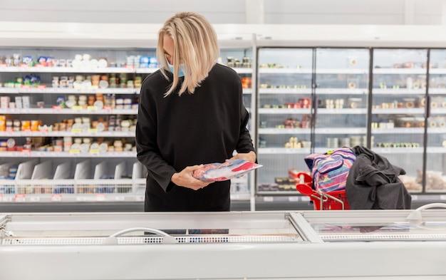 Młoda kobieta w masce medycznej w dziale mrożonek w dużym supermarkecie światła