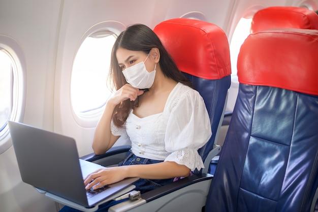 Młoda kobieta w masce na twarz korzysta z laptopa na pokładzie. nowa normalna podróż po koncepcji pandemii covid-19