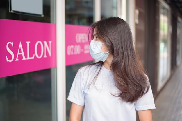 Młoda kobieta w masce ochronnej covid-19 stoi przed salonem kosmetycznym