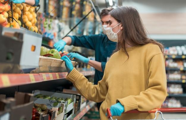 Młoda kobieta w masce ochronnej kupuje jabłka