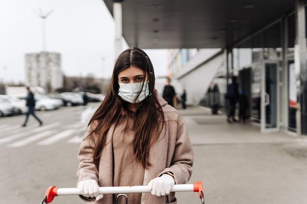 Młoda kobieta w masce ochronnej przed koronawirusem 2019-ncov pcha wózek na zakupy.