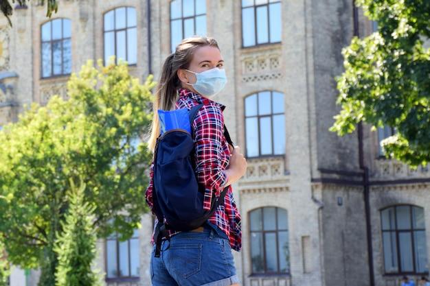 Młoda kobieta w masce ochronnej stoi na zewnątrz w pobliżu uniwersytetu. powrót do szkoły po kwarantannie. nowa normalność.