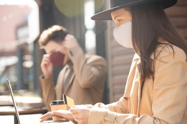 Młoda kobieta w masce ochronnej trzyma kartę kredytową podczas zakupów online przed laptopem i zamierza dokonać płatności