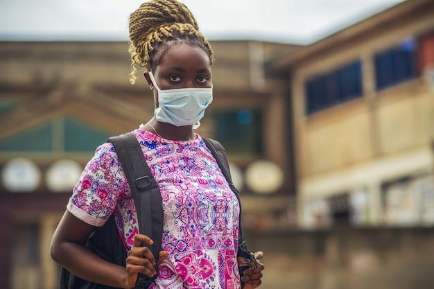 Młoda kobieta w masce ochronnej z plecakiem na zewnątrz