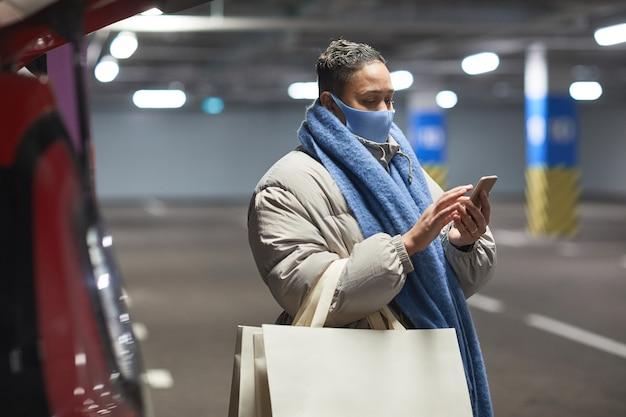 Młoda kobieta w masce ochronnej z torby na zakupy przy użyciu telefonu komórkowego, stojąc w podziemnym parkingu