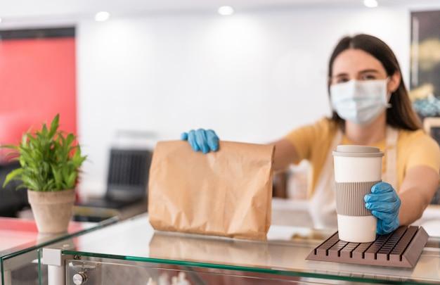 Młoda kobieta w masce podczas serwowania śniadania i kawy na wynos w restauracji bufetowej - pracownik przygotowuje jedzenie w barze piekarni podczas okresu koronawirusa - skoncentruj się na prawej ręce