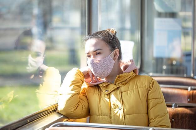 Młoda kobieta w masce siedzi samotnie w środkach transportu publicznego