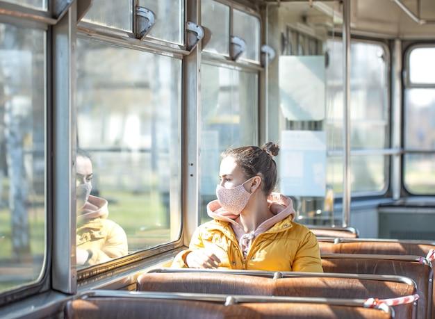 Młoda kobieta w masce siedzi samotnie w transporcie publicznym podczas pandemii koronawirusa.