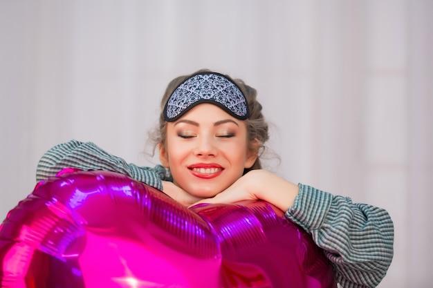 Młoda kobieta w masce snu przytula balon różowy serce i uśmiecha się z zamkniętymi oczami