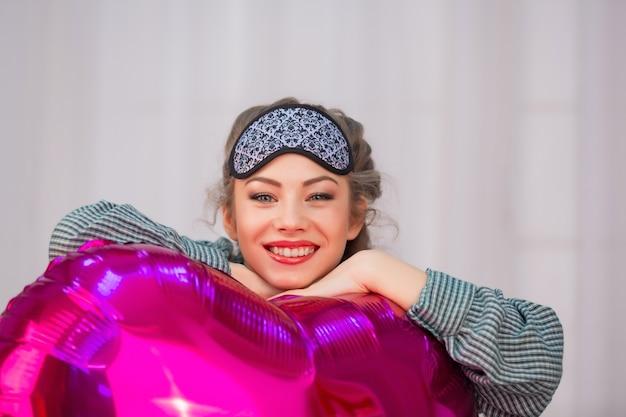 Młoda kobieta w masce snu przytula różowy balon w kształcie serca i uśmiecha się