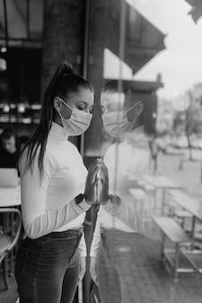 Młoda kobieta w masce stojącej przed oknami w kawiarni