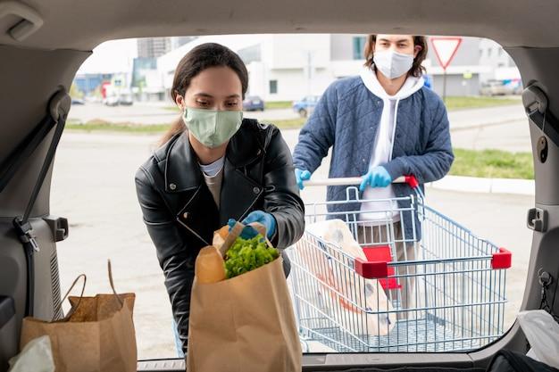 Młoda kobieta w masce wkłada papierowe torby pełne produktów do samochodu, podczas gdy chłopak stoi z wózkiem za nią