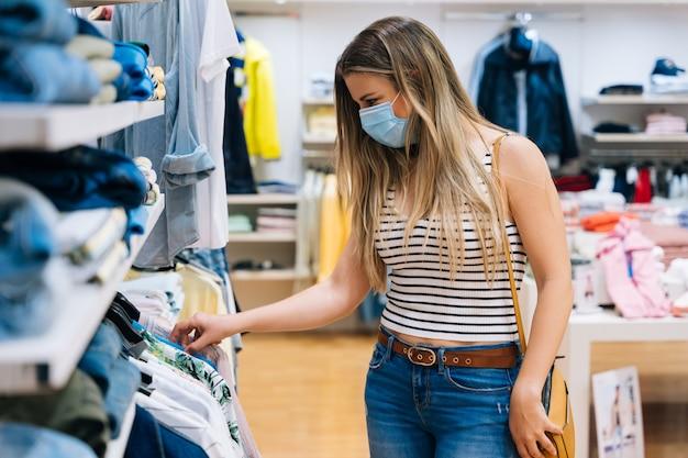 Młoda kobieta w masce zakupy w sklepie odzieżowym w pandemii koronawirusa