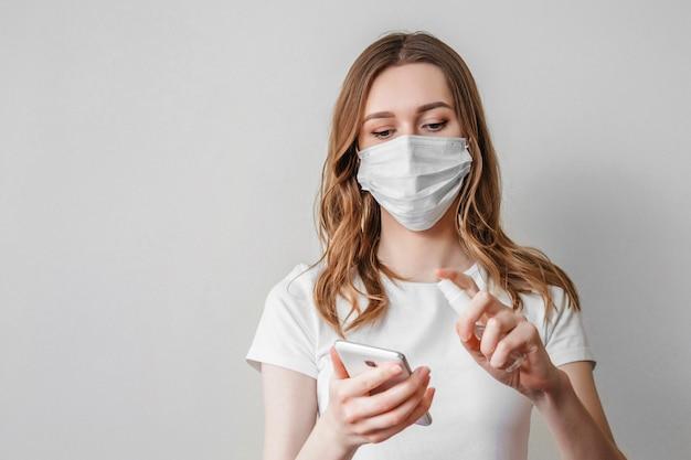 Młoda kobieta w medycznej masce myje telefon komórkowy roztworem antyseptycznym w aerozolu