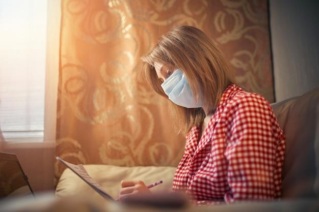 Młoda kobieta w medycznej masce ochronnej działa w domu