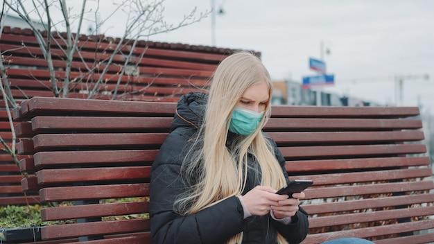 Młoda kobieta w medycznym maskowym obsiadaniu na ławce i używać telefonie