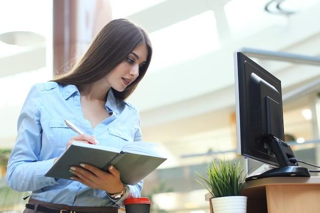 Młoda kobieta w miejscu pracy przegląda notatki w pamiętniku.