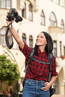 Młoda kobieta w mieście bierze selfie.