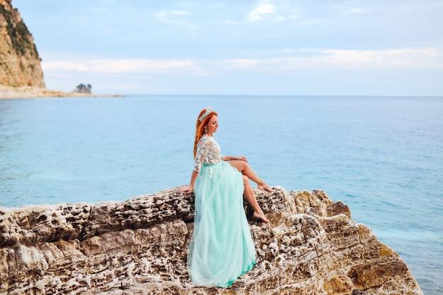Młoda kobieta w miętowej sukience siedzi na dużym kamieniu na brzegu morza adriatyckiego