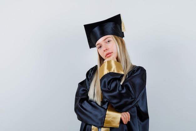 Młoda kobieta w mundurze absolwenta podpierająca podbródek na dłoni i wyglądająca uroczo