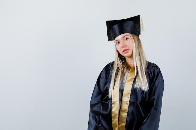 Młoda kobieta w mundurze absolwenta pozuje patrząc w kamerę i wygląda rozsądnie