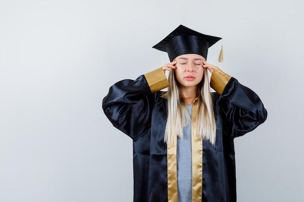 Młoda kobieta w mundurze absolwenta, trzymająca palce na skroniach i wyglądająca na zmęczoną