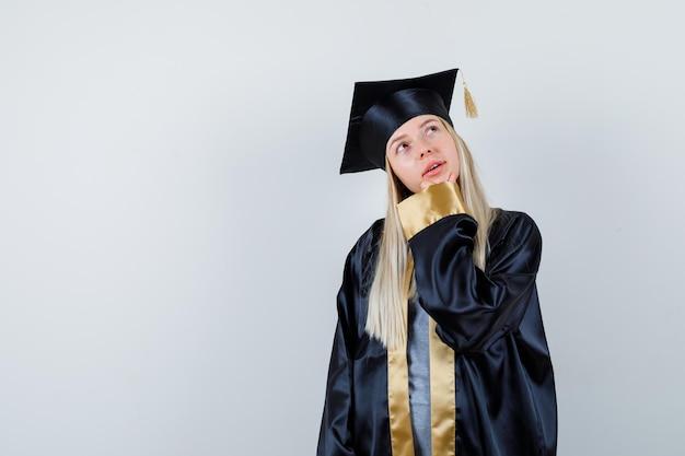 Młoda kobieta w mundurze absolwenta, trzymająca rękę na brodzie i patrząca zamyślona