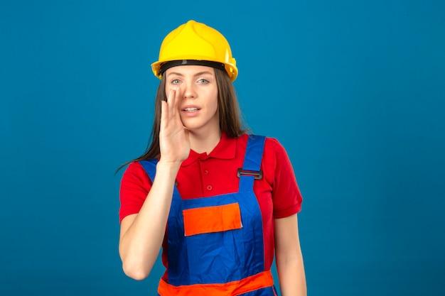 Młoda kobieta w mundurze budowy i żółty kask z ręką w pobliżu ust mówi tajemnicy stojącej na niebieskim tle