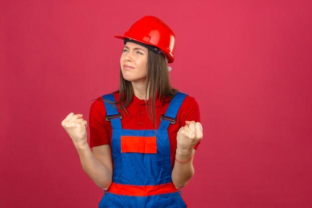Młoda kobieta w mundurze konstrukcyjnym i czerwonym kasku z podniesionymi pięściami niezadowolona i sfrustrowana czymś stojącym na ciemnoróżowym tle