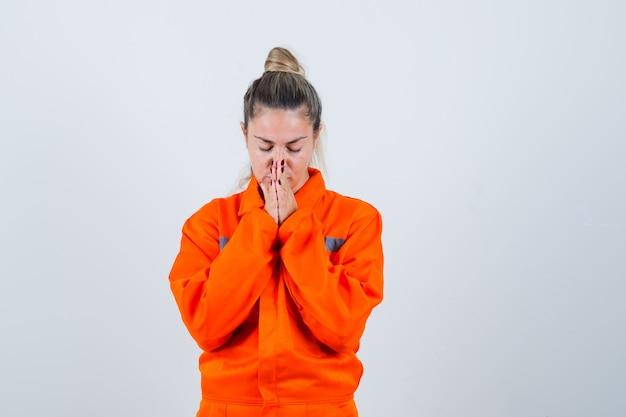 Młoda kobieta w mundurze pracownika modląc się i patrząc skoncentrowany, widok z przodu.