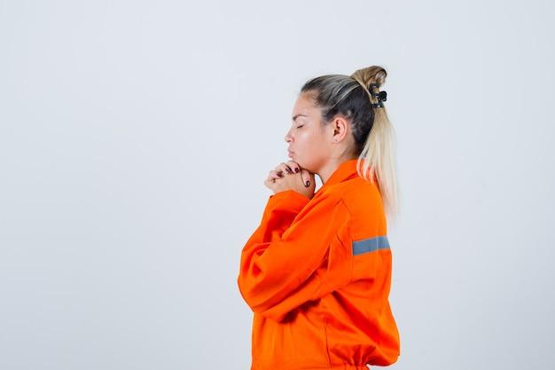 Młoda kobieta w mundurze pracownika modląc się i patrząc z nadzieją.