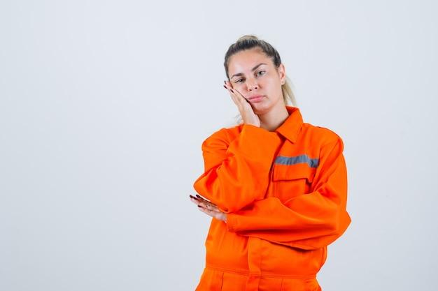 Młoda kobieta w mundurze pracownika, opierając się pod ręką, wyrażając brak zainteresowania i wyglądający tępo, widok z przodu.