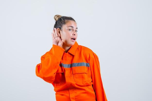 Młoda kobieta w mundurze pracownika słuchania dźwięków i patrząc skoncentrowany, widok z przodu.