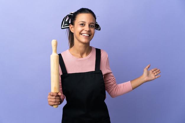 Młoda kobieta w mundurze szefa kuchni wyciągając ręce na bok za zaproszenie do przyjścia