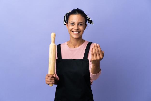 Młoda kobieta w mundurze szefa kuchni, zachęcając do przyjścia z ręką. cieszę się, że przyszedłeś