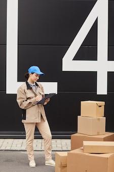 Młoda kobieta w mundurze wypełnia dokument i przyjmuje paczki, stojąc naprzeciw magazynu