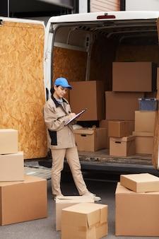 Młoda kobieta w mundurze wypełnia formularz i sprawdza paczki przed dostarczeniem, stojąc na zewnątrz