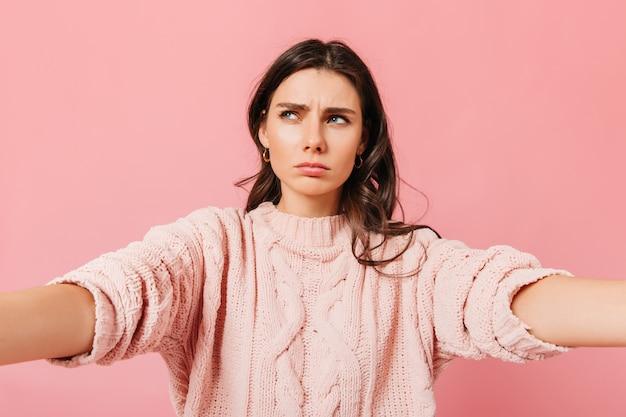 Młoda kobieta w myśli sprawia, że selfie na różowym tle. dziewczyna z falowanymi włosami pozowanie do selfie.