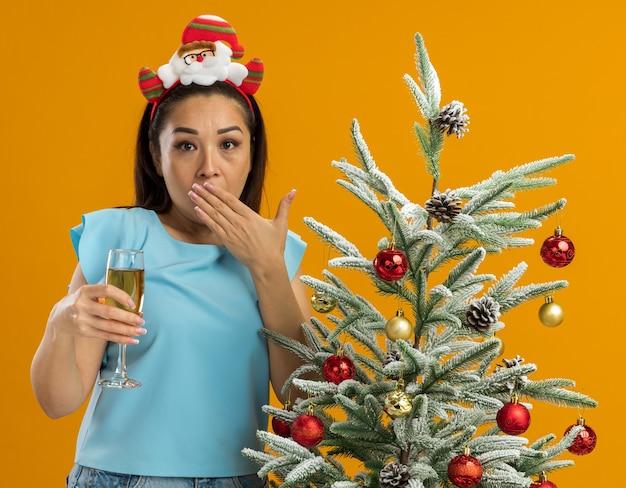 Młoda kobieta w niebieskiej bluzce ubrana w zabawną świąteczną obwódkę na głowie trzymająca kieliszek szampana patrząc na kamerę zszokowana zakrywająca usta ręką stojącą obok choinki na pomarańczowym tle