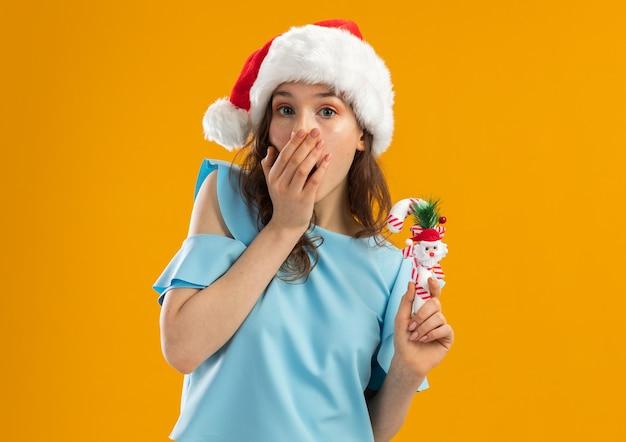 Młoda kobieta w niebieskiej górze i santa hat trzyma bożonarodzeniową laskę kandyzowaną, patrząc zszokowany obejmując usta ręką