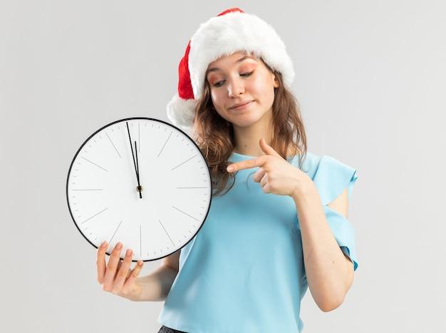 Młoda kobieta w niebieskiej górze i santa hat trzyma zegar ścienny wskazując palcem wskazującym na to uśmiechnięty pewnie
