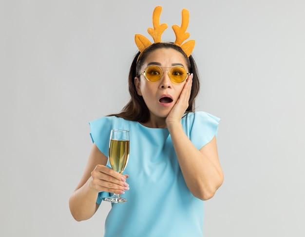 Młoda kobieta w niebieskiej górze ubrana w zabawną obręcz z rogami jelenia i żółte okulary trzyma kieliszek szampana, patrząc zdziwiony i zaskoczony
