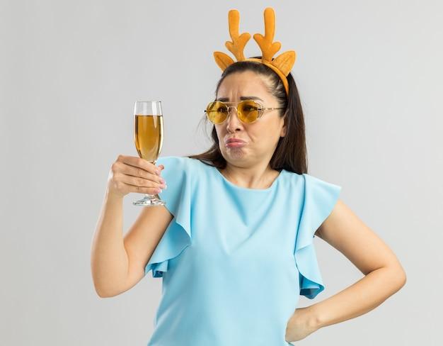 Młoda kobieta w niebieskiej górze ubrana w zabawną obręcz z rogami jelenia i żółtymi okularami trzymająca kieliszek szampana, patrząc na niego zdezorientowana i niezadowolona